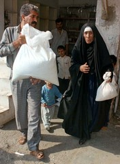 An Iraqi man and his mother collect their monthly food ration in Baghdad on November 2. Iraqi's fear..