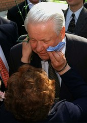 A woman wipes off lipstick from the face of Russian President Boris Yeltsin after giving him a kiss ..