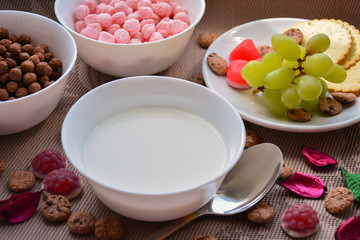 Milk, crispy colorful balls and grapes for breakfast