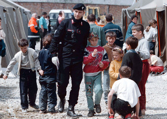 An Italian Carabinieri walks with young ethnic Albanians refugees at a refugee camp in the suburbs ..