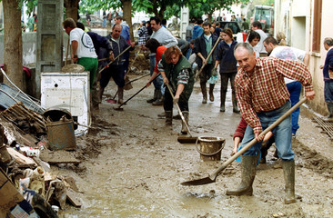 RESIDENTS SHOVEL MUD AWAY AFTER FLOODS.