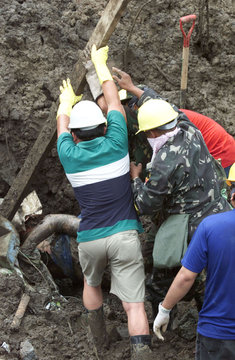 FILIPINO RESCUERS USE A WOOD TO PULLOUT A MALE BODY.