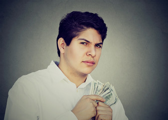 Greedy suspicious man holding money dollar bills in hand