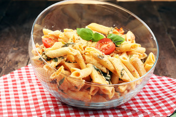 Penne pasta in tomato sauce with chicken, tomatoes decorated with basil on a wooden table