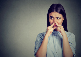Woman pinches nose with fingers looks with disgust sideway something stinks bad smell