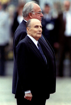 German Chancellor Helmut Kohl (background) and French President Francois Mitterrand listen to the na..