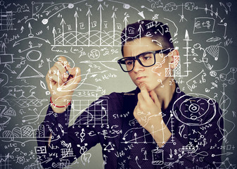 Smart business man writing formulas or science financial calculations