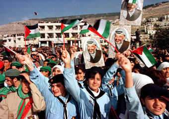 Palestinian school girls cheer PLO chairman Yasser Arafat with flags and posters on arrival at the n..