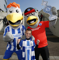 A Brighton fan poses for a photograph with the club mascots outside the stadium before the match