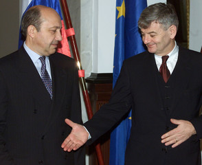 German Foreign Minister Joschka Fischer (R) reaches out to exchange a handshake with Russia's counte..