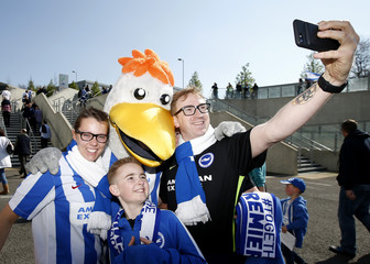 Brighton fans pose for a photograph with the club mascot outside the stadium