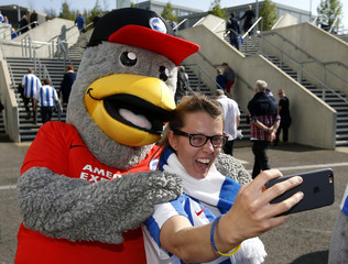 Brighton fan poses for a photograph with the club mascot outside the stadium before the start of the match