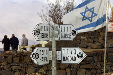 A signpost points out that Damascus is a mere 60 kms from the Golan Heights as Israeli tourists view..