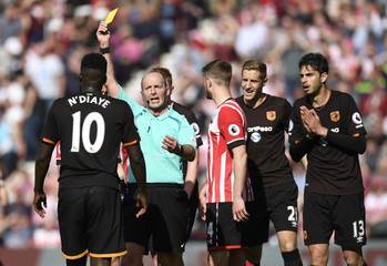 Hull City's Alfred N'Diaye is shown a yellow card by referee Mike Dean