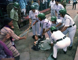 Policewomen use batons to disperse women activists of the Socialist Unity Centre of India party (SUC..