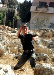 A Palestinian young man hurls a rock at Israeli soldiers with a sling during clashes in this town on..