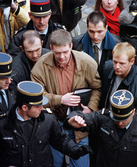 Princess Diana's bodyguard Trevor Rees-Jones (C) is surrounded by police, bodyguards  and journalist..