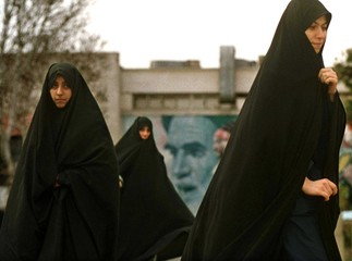 GIRLS WALK IN FRONT OF POSTER OF AYATOLLAH KHOMEINI.