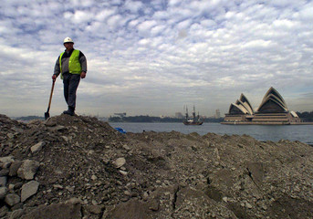 WORKER STANDS ON TOP OF SOIL BEING TRANSPORTED BY BARGE ON SYDNEY HARBOUR.