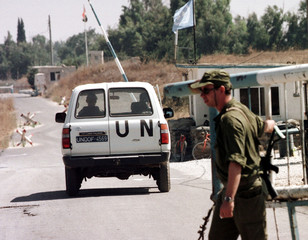 An Israeli soldier opens the gate at the Kuneitra border crossing to allow an United Nations van to ..