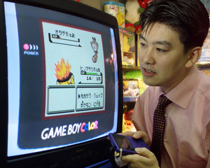 NINTENDO SALESMAN HATAKEYAMA DEMONSTRATES NEWLY-LAUNCHED POKEMON VIDEO GAME SOFTWARE IN TOKYO.