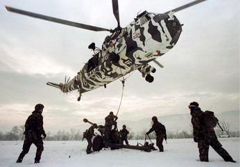A Royal Navy Seaking helicopter, painted in IFOR arctic camoflauge, lands a 105mm Light Gun to troop..