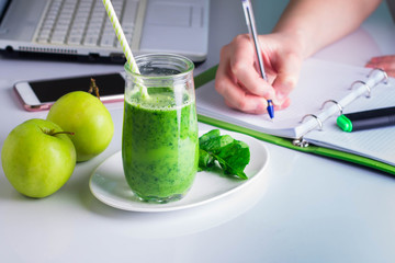 Freelancer Woman right hand writing on notebook and laptop, mobile smart phone nearby.Healthy Drink Smoothie from Green Spinach