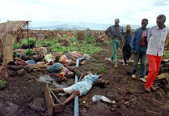 Rwandan Hutu refugees pass by a group of massacred women and children inside the Mugunga camp near t..