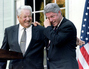 U.S. President Bill Clinton wipes away tears of laughter as he leans on Russian President Boris Yelt..