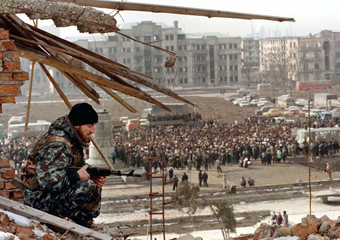 A Chechen fighter keeps watch from a destroyed building in central Grozny over an election rally of ..