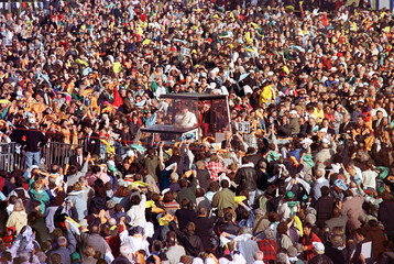 Pope John Paul II is driven through the huge crowd to a podium where he will serve an open air mass ..