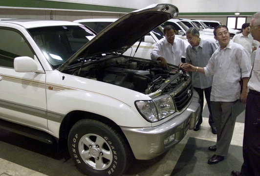 Filipino bidders inspect an engine compartment of one of 10 smuggled luxury cars which the Philippin..