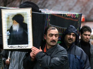 Iraqi men carry a coffin with the portrait of murdered spiritual leader Ayatollah Mohammed Sadeq al-..