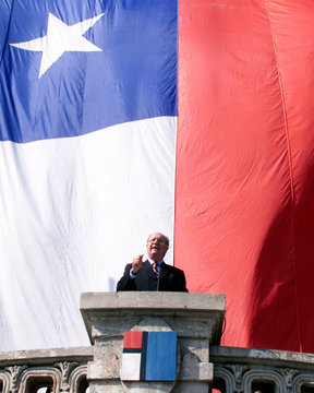 CHILEAN PRESIDENTIAL CANDIDATE LAGOS SPEAKS FROM BALCONY WITH GIANT CHILEAN FLAG AS BACKGROUND.