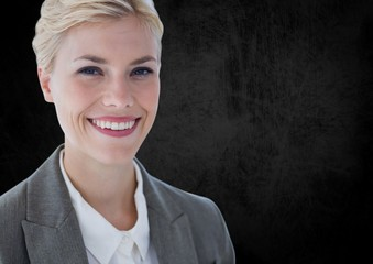 Business woman smiling against black wall