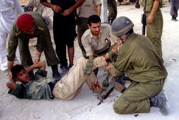 An Israeli soldier puts a dressing on a wounded Palestinian's leg as a Palestinian policeman comfort..