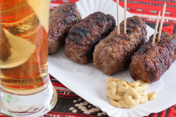 Fototapete - delicious roasted meat rolls romanian mititei mici with mustard and glass of beer