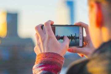 Young woman takes pictures of the city on a smartphone