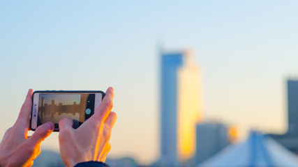 Hands make a city photo on a smartphone. Blurred business center background. Gadgets on hand concept