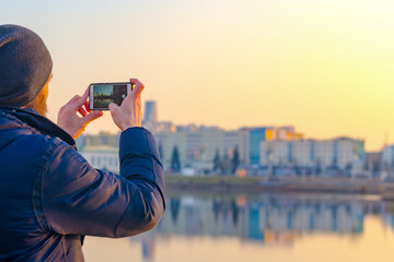 Young man in hat takes pictures of the city's panorama on a smartphone. City travel concept