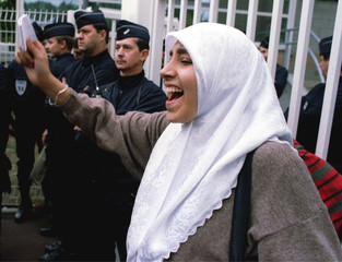 A young muslim girl wearing a headscarf shouts as French riot police stand near the gates of a high ..