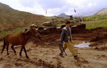 An Iraqi Kurdish boy pulling his horse walks past a group of Turkish army tanks positioned in the Pi..