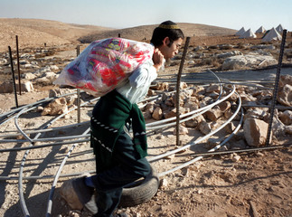 JEWISH SETTLER CARRIES BAG OF BREAD PAST OBSTACLES AT MAON FARM.