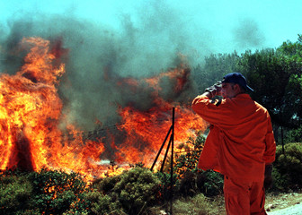 A Greek fireman protects his face from the heat generated by a blazing forest fire on the outskirts ..
