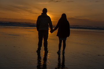 couple holding hands at beach at sunset