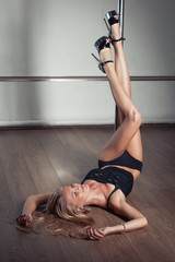 Sexy slim pole dance blonde girl with long legs lying on the floor near the pole