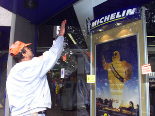 A worker  from the Michelin tyre factory puts union stickers on the entrace to  the groups headquart..