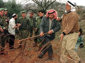 Naim Zalloun, a Palestinian who lives adjacent to the Jewish settlement town of Kiryat Arba on the o..