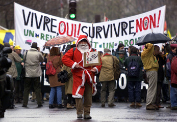 A French jobless demontrator dressed as Santa Claus leads a protest march December 11. Thousands of ..