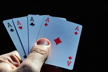 Four aces from canasta joker from 52 card French deck held in male left hand on dark background